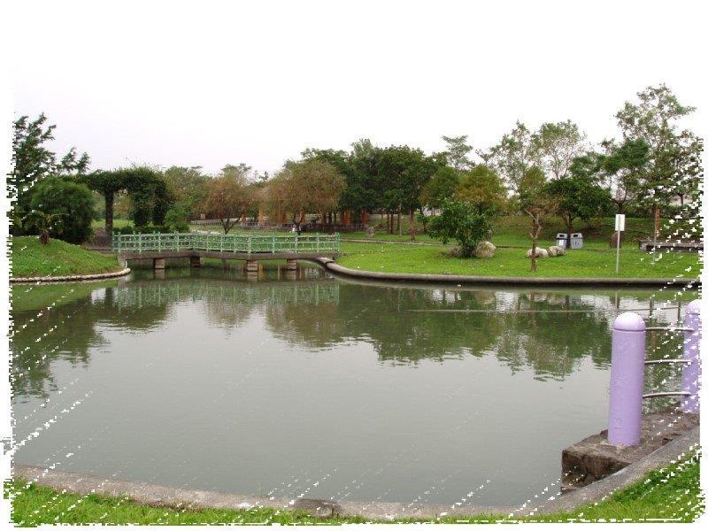此為分洪堰風景區裡的湖畔邊遠眺一座翠綠色欄杆的小橋,背景有許多綠樹。