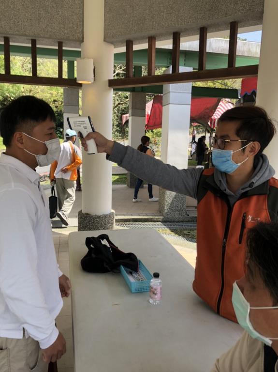 配合中央防疫政策,在納骨塔(廊)出入口處對民眾量測額溫。